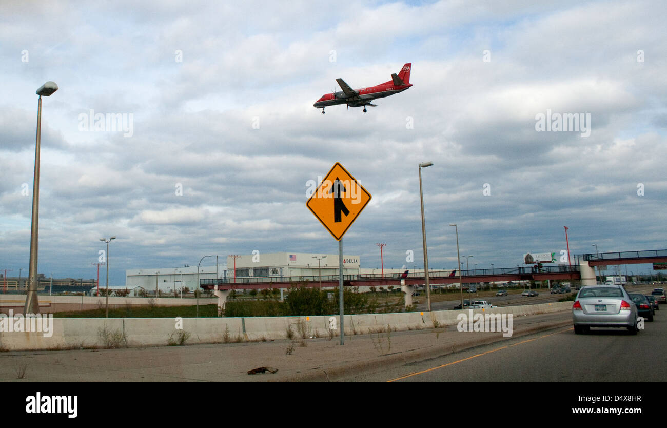NW (now Delta) Airlink turboprop airplane flying over freeway 494 near the international airport. Minneapolis Minnesota - Stock Image