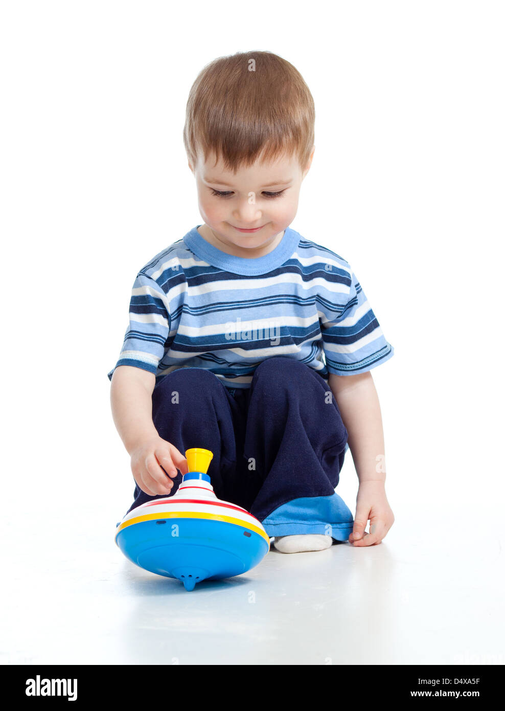 Cute little child is playing with toys while sitting on floor, isolated over white - Stock Image