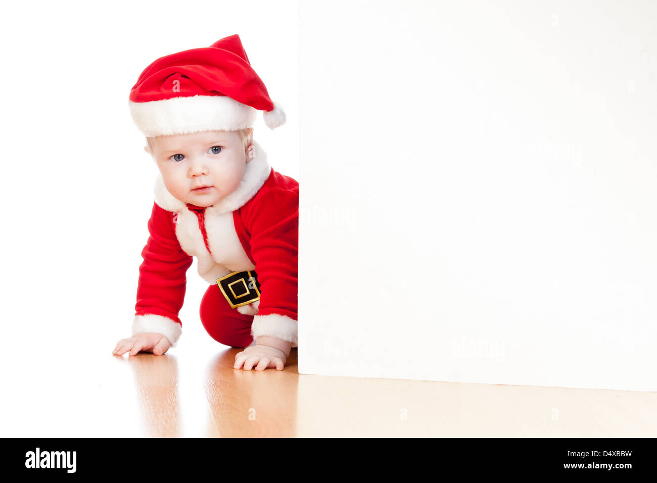 small Santa claus child looking from behind the placard - Stock Image