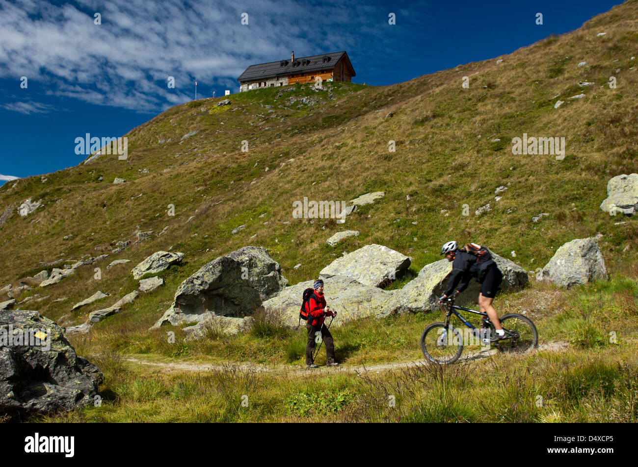 Encounter between a hiker and a mountain biker on a hiking trail, Verbier, Valais, Switzerland - Stock Image