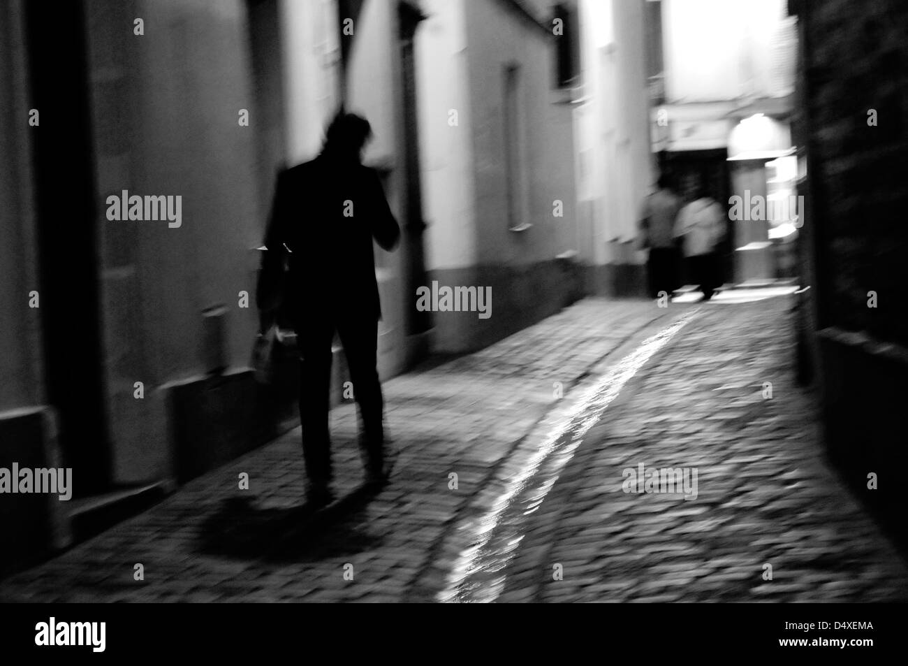 A man walks in a alleyway at night in Montmartre, Paris, France. - Stock Image