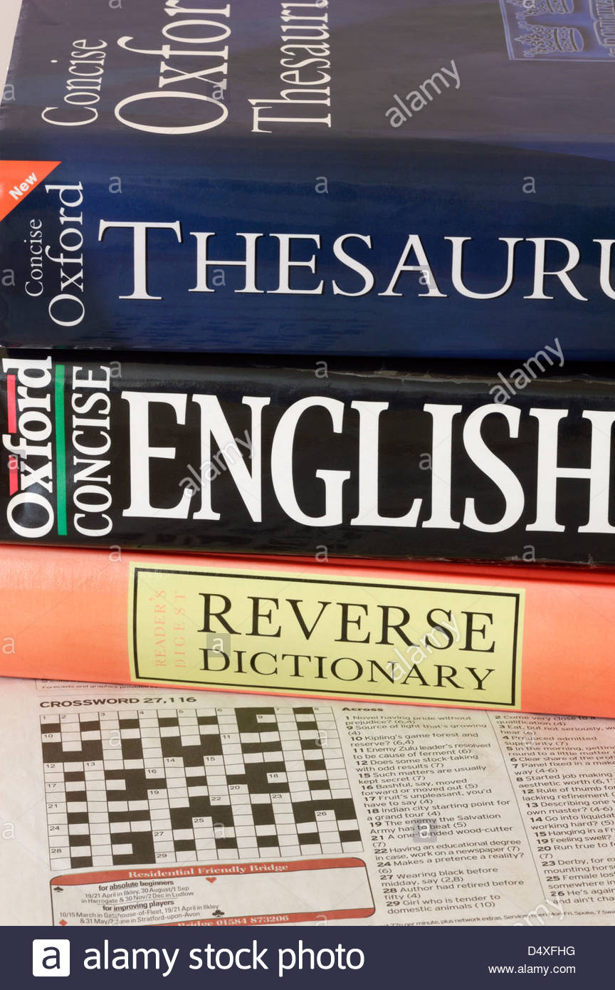 Newspaper crossword puzzle with reference books - Stock Image
