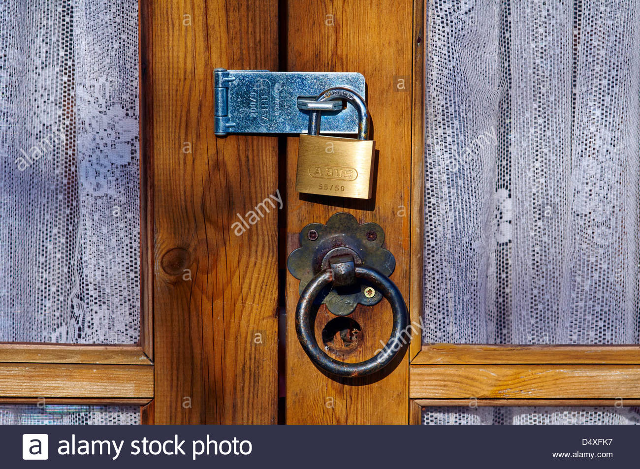 brass padlock steel lock on a wooden door with glass panels and net curtains on the windows - Stock Image
