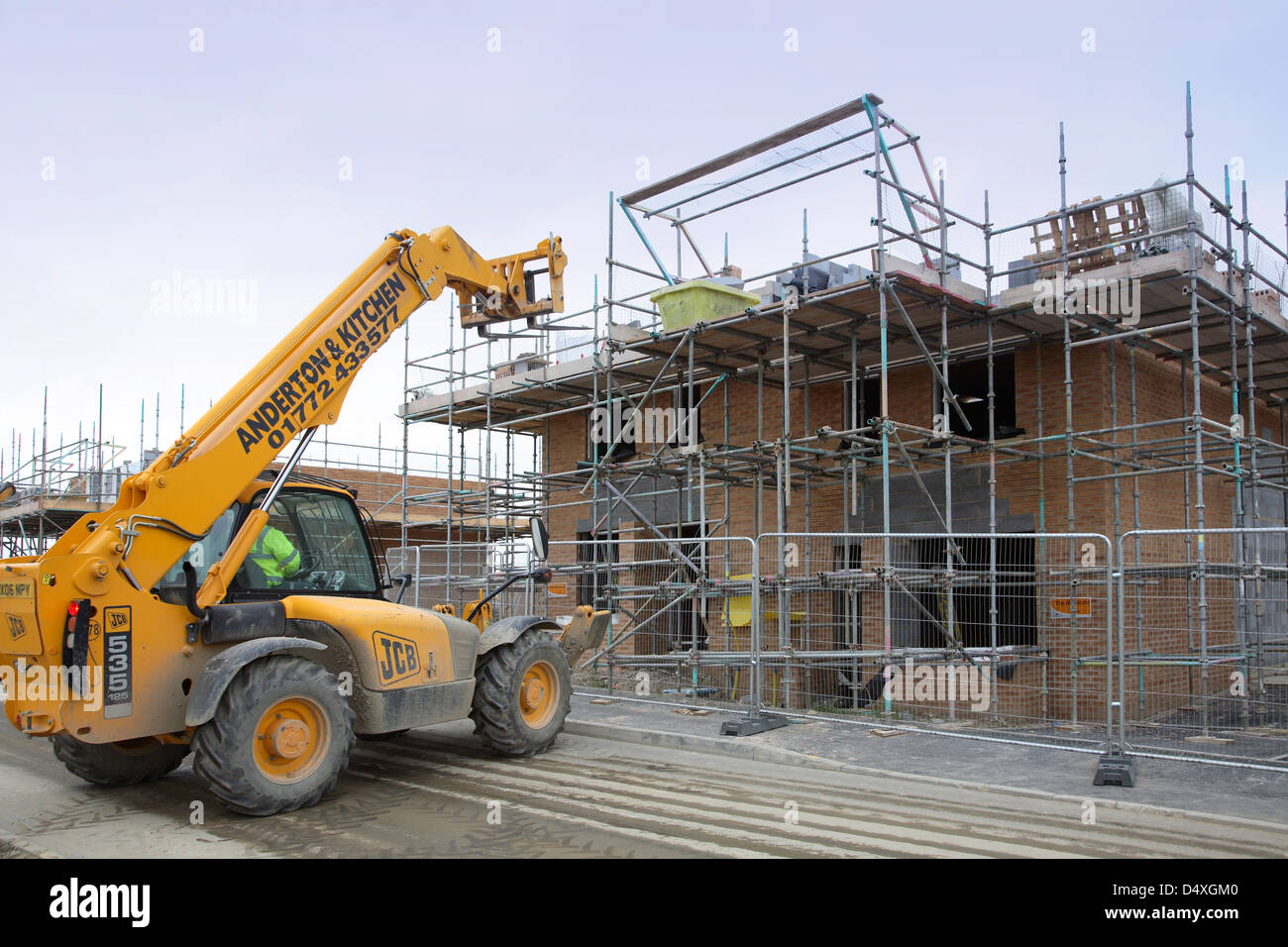 Construction of traditional  two storey, brick housing in Sheffield, UK. A telehandler loads materials onto the - Stock Image
