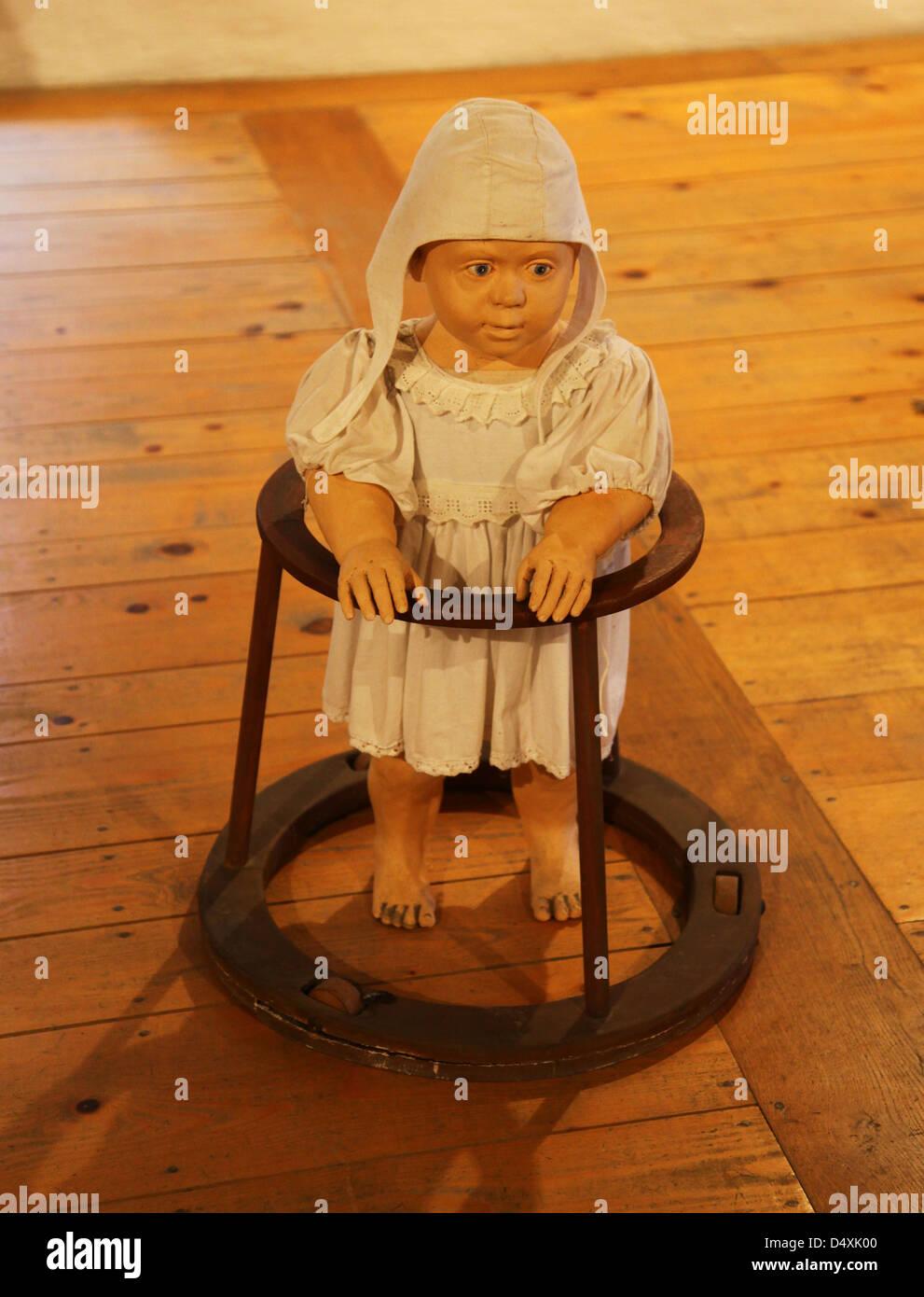 A doll in a medieval baby walker inside Predjama Castle Slovenia - Stock Image