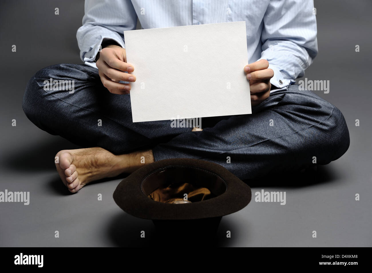 An image of a beggar with a hat and a sheet of paper - Stock Image