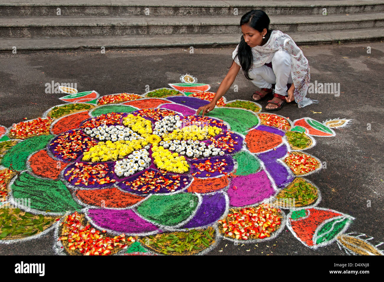 Chennai woman is making an Rangoli design with Flowers in an Indian street  during the hindu festival of Sankranthi Stock Photo