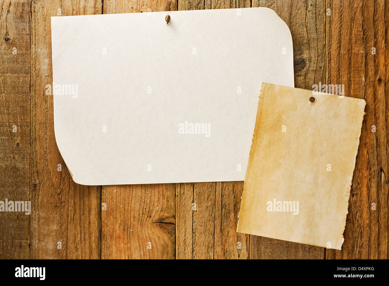 mottled beige parchment paper posters similar to the grungy cowboy wanted notices nailed to vintage wooden planks - Stock Image