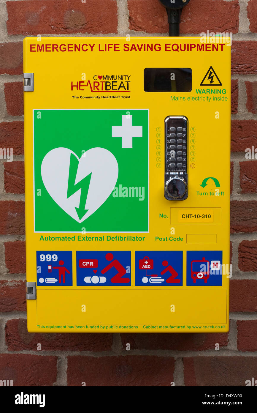 Emergency defibrillator in a bright yellow box on the wall of a sports centre Stock Photo