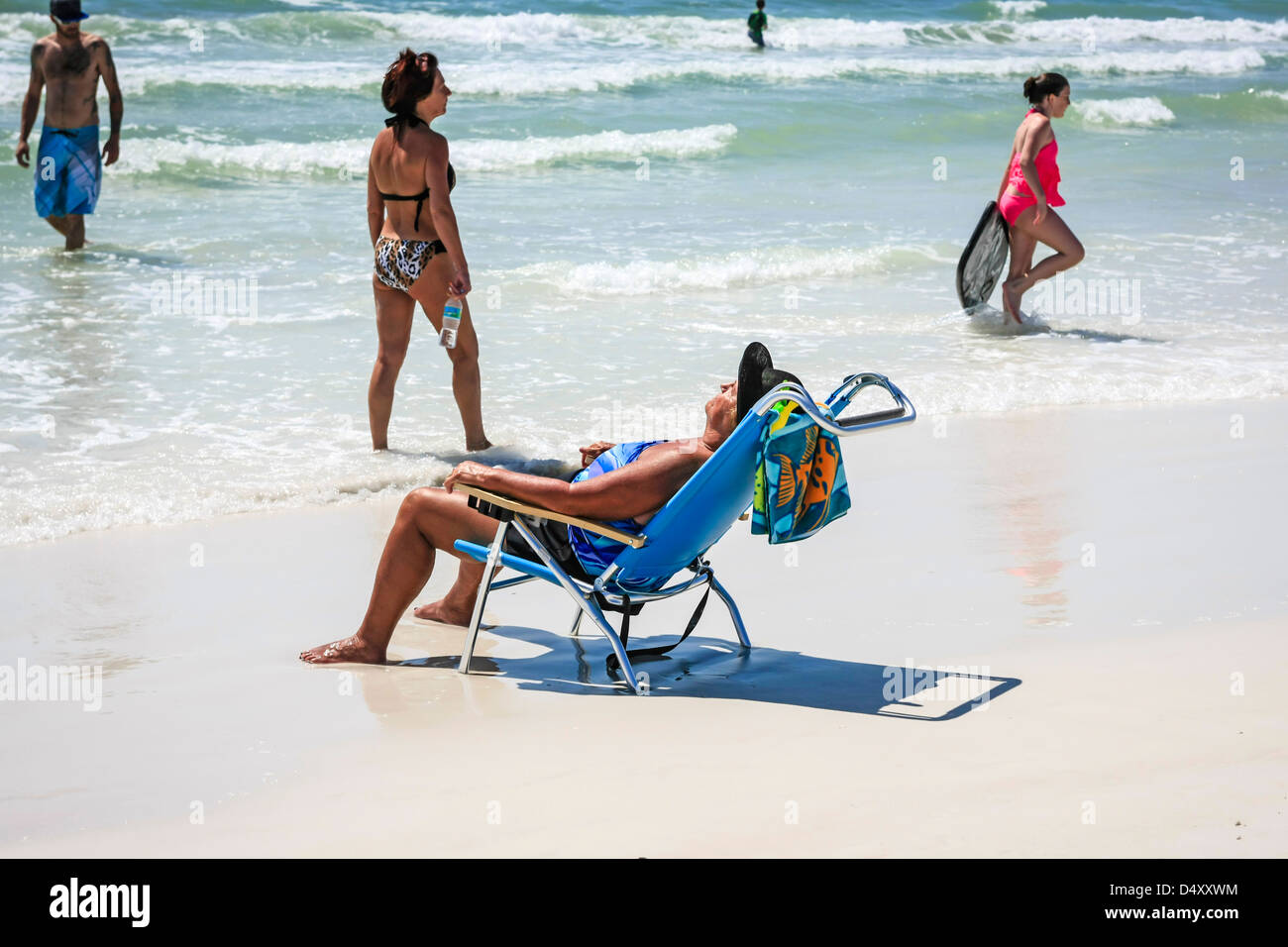 Female retiree enjoying the sunshine on Siesta Key beach Florida during Spring Break - Stock Image