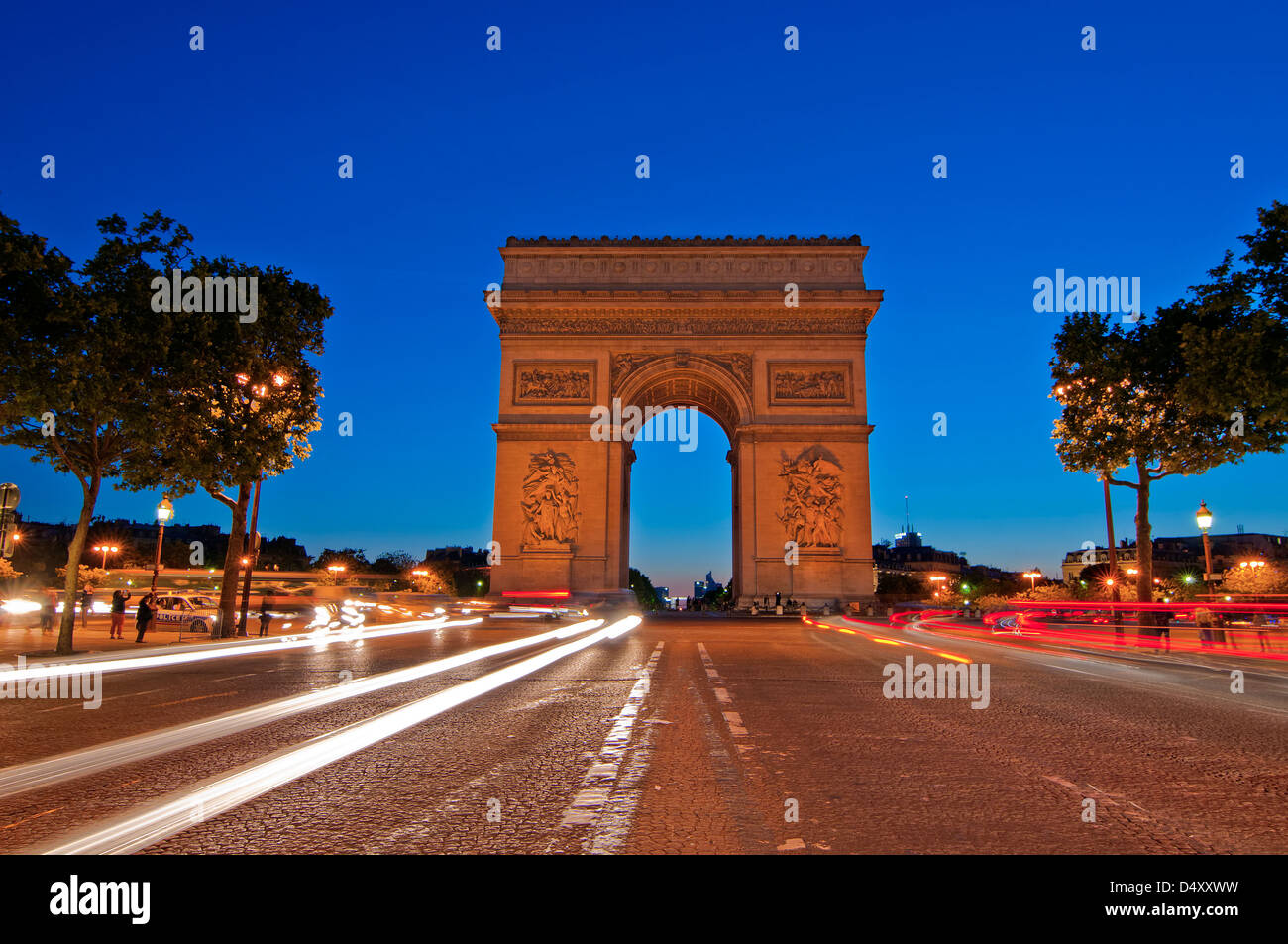 Light trail image in the front of the landmark Arc de Triomphe at night time in Paris, France. - Stock Image