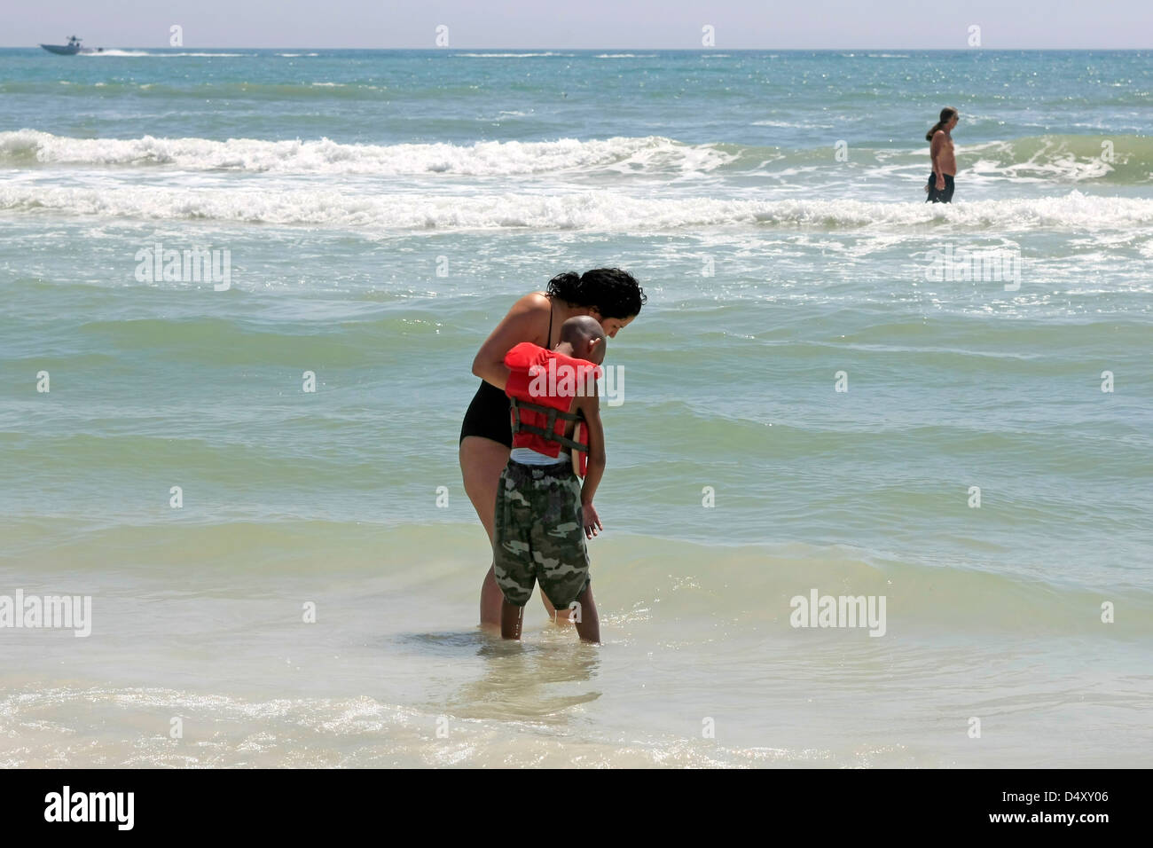 Woman with a disabled child enjoying the sunshine on Siesta Key beach Florida during Spring Break - Stock Image