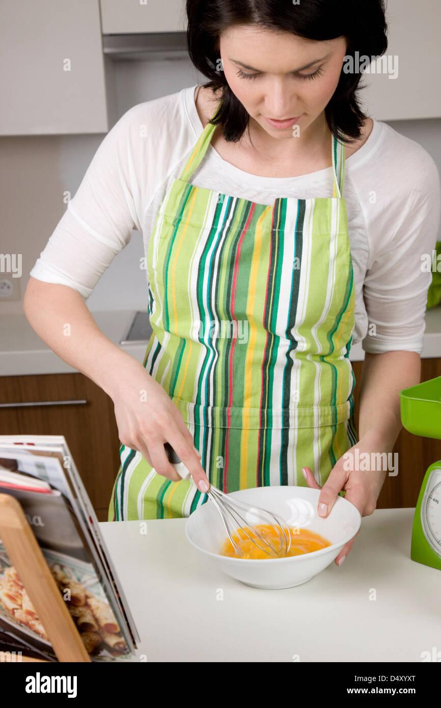 Woman whisking the egg yolks - Stock Image