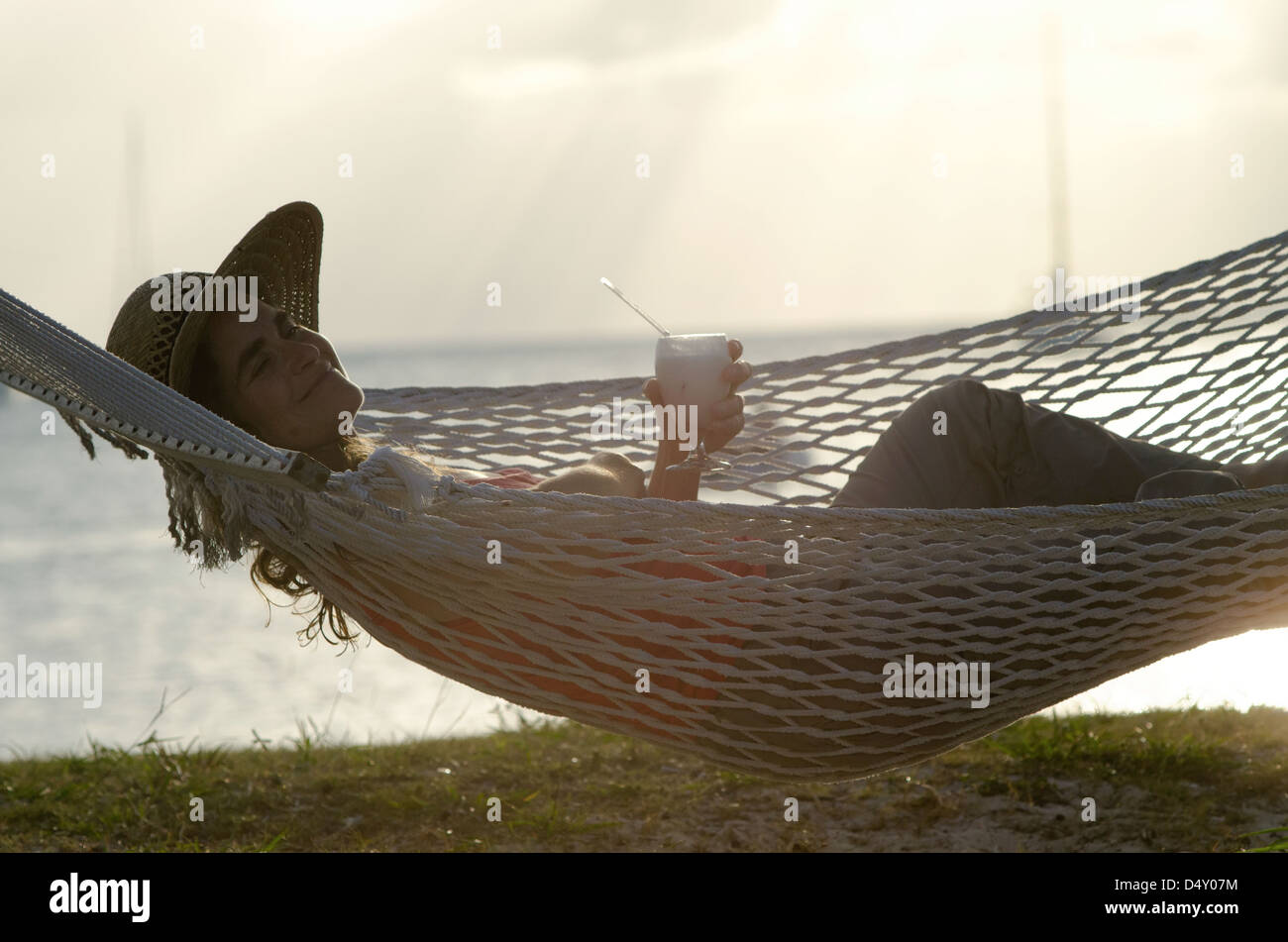 Relaxing in a hammock with a cocktail on the beach of Anegada, British Virgin Islands. - Stock Image