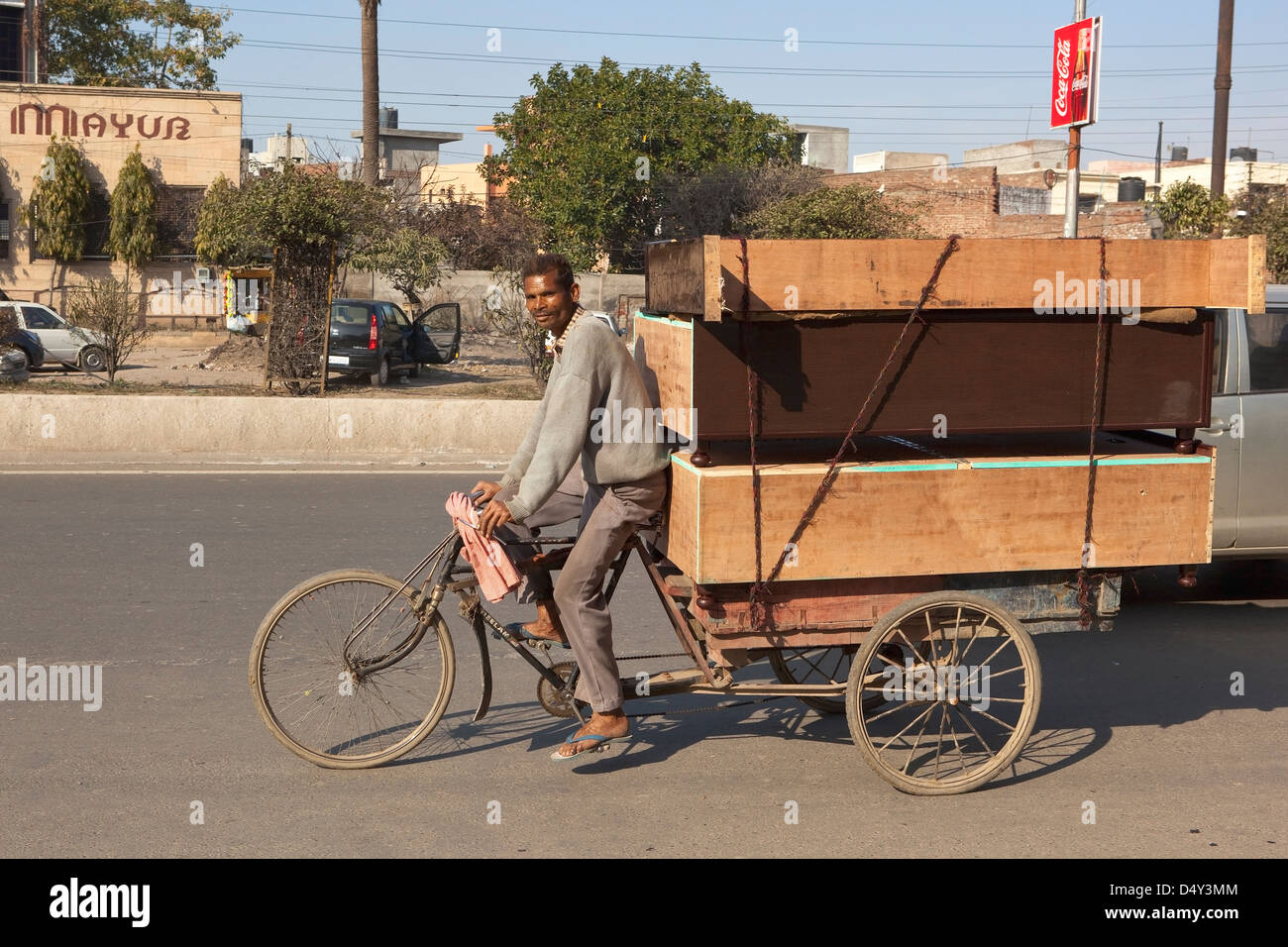 Amritsar street scene with a Punjabi man carrying furniture on a rickshaw on his way home on a sunny evening - Stock Image