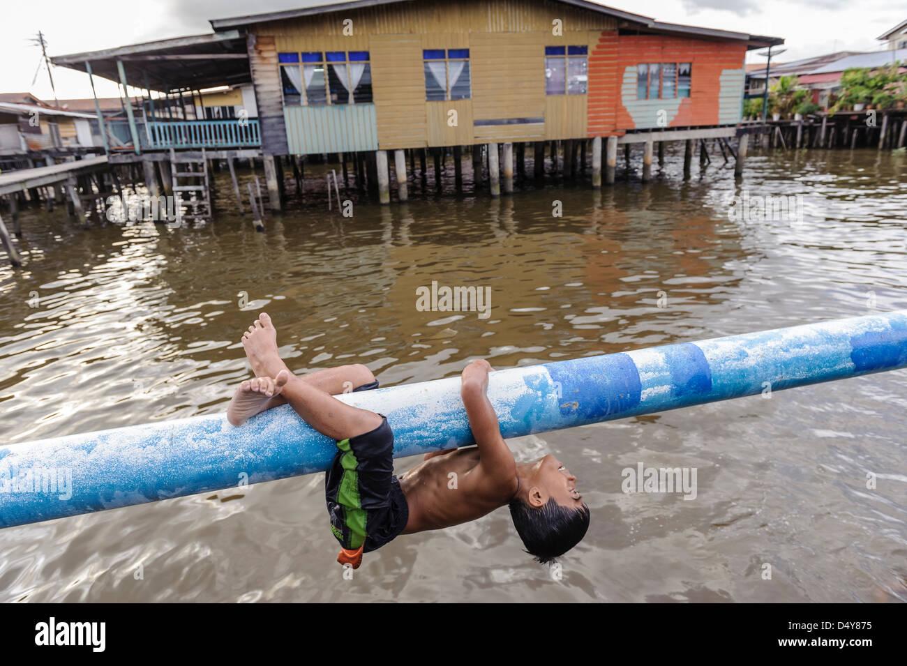 Boy playing and swimming, Kampung Ayer neighbourhood, Bandar Seri Bengawan, Brunei, Asia - Stock Image