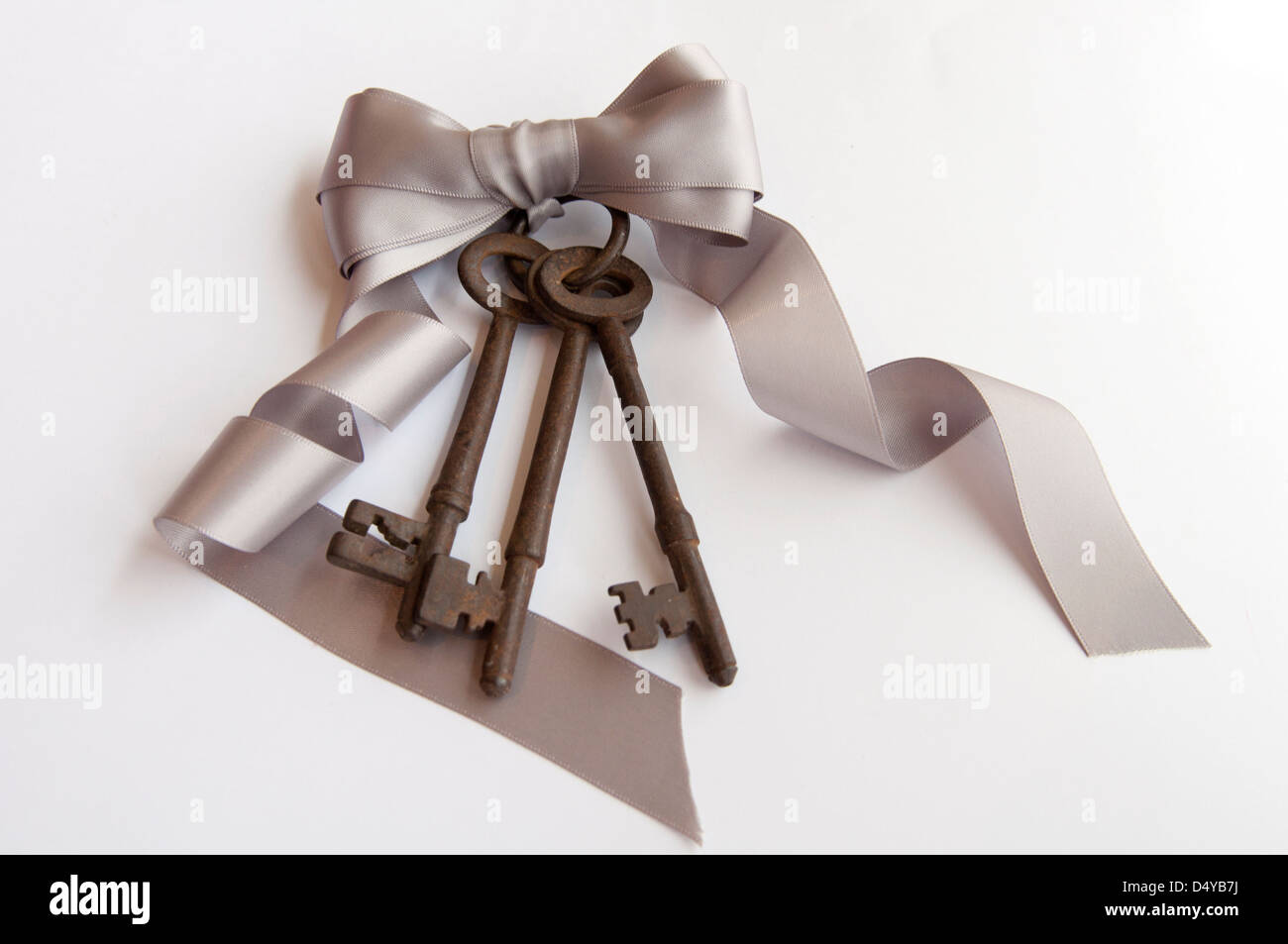 Three rusty antique vintage keys tied with keyring on silk silver ribbon bow - Stock Image