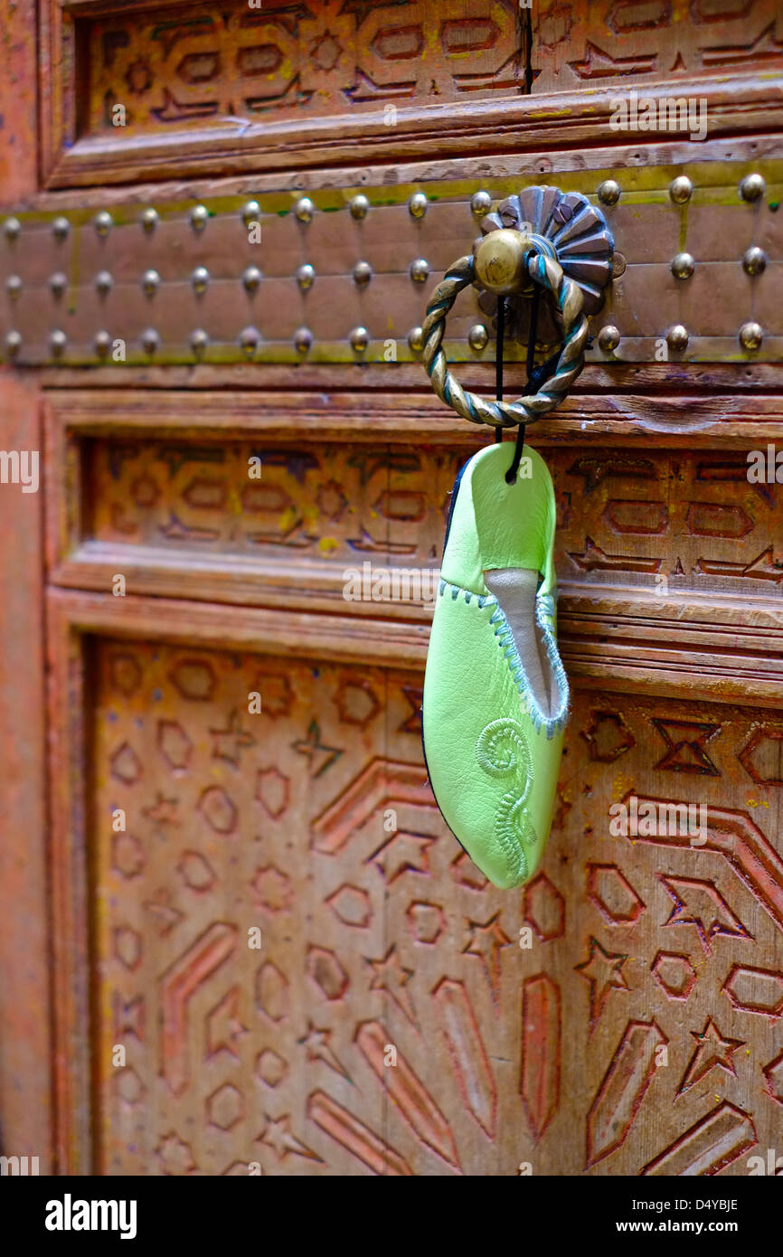 A Moroccan babouche toy shoe hanging on a traditional riyadh carved wooden painted door. - Stock Image