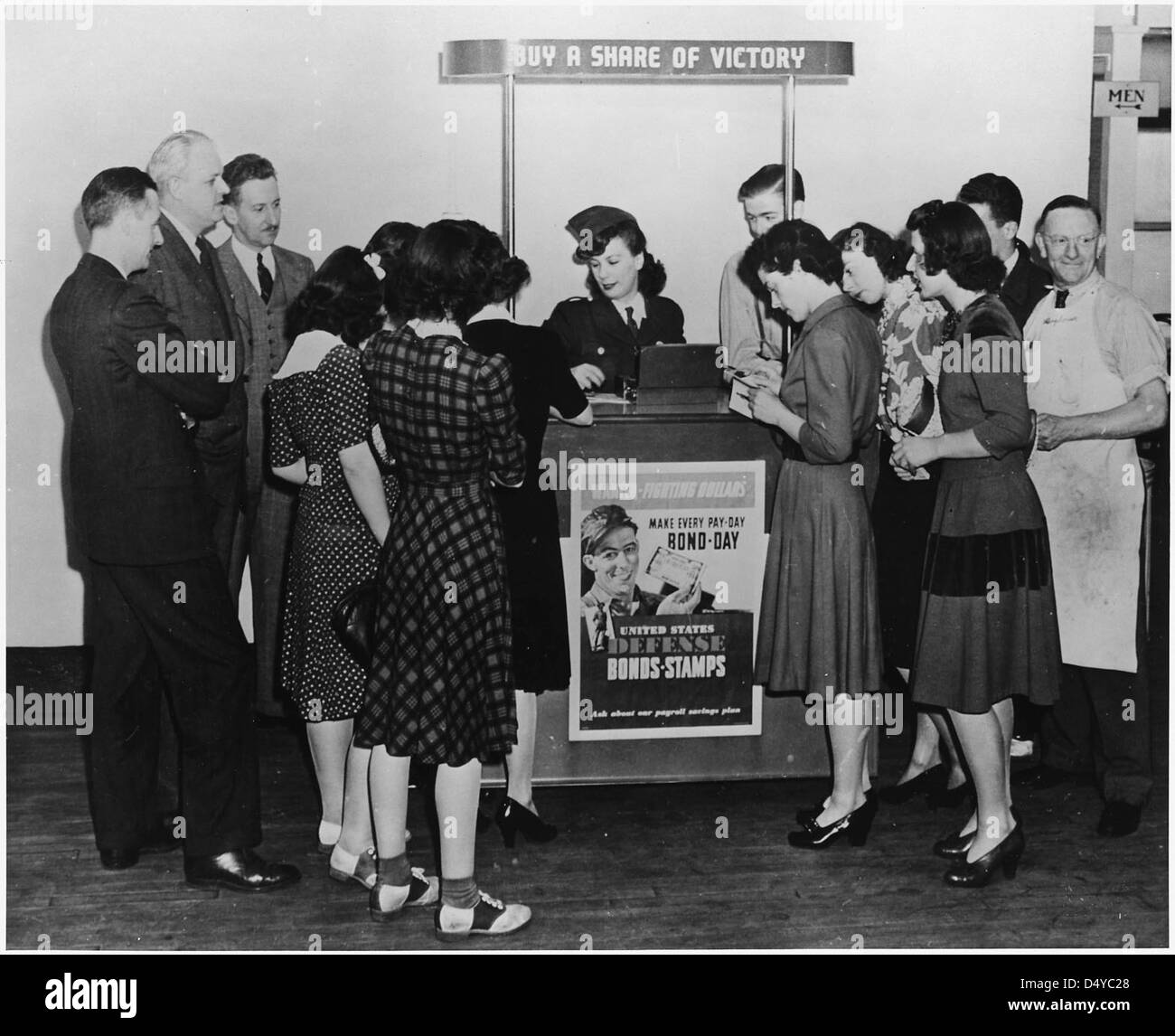 A young woman sells war bonds and stamps and distributes War Production Drive literature., ca. 1943 - Stock Image