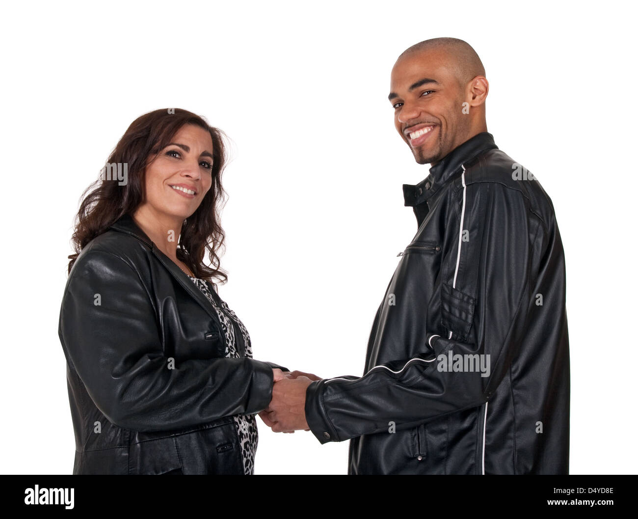 Multicultural couple holding hands and smiling. Mature woman with younger man. - Stock Image