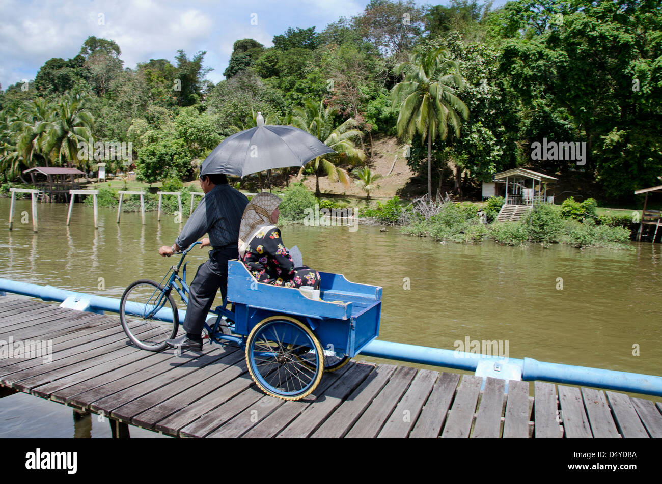Borneo, Brunei Darussalam. District of Bandar Seri Begawan. Man on bicycle with woman on back. - Stock Image