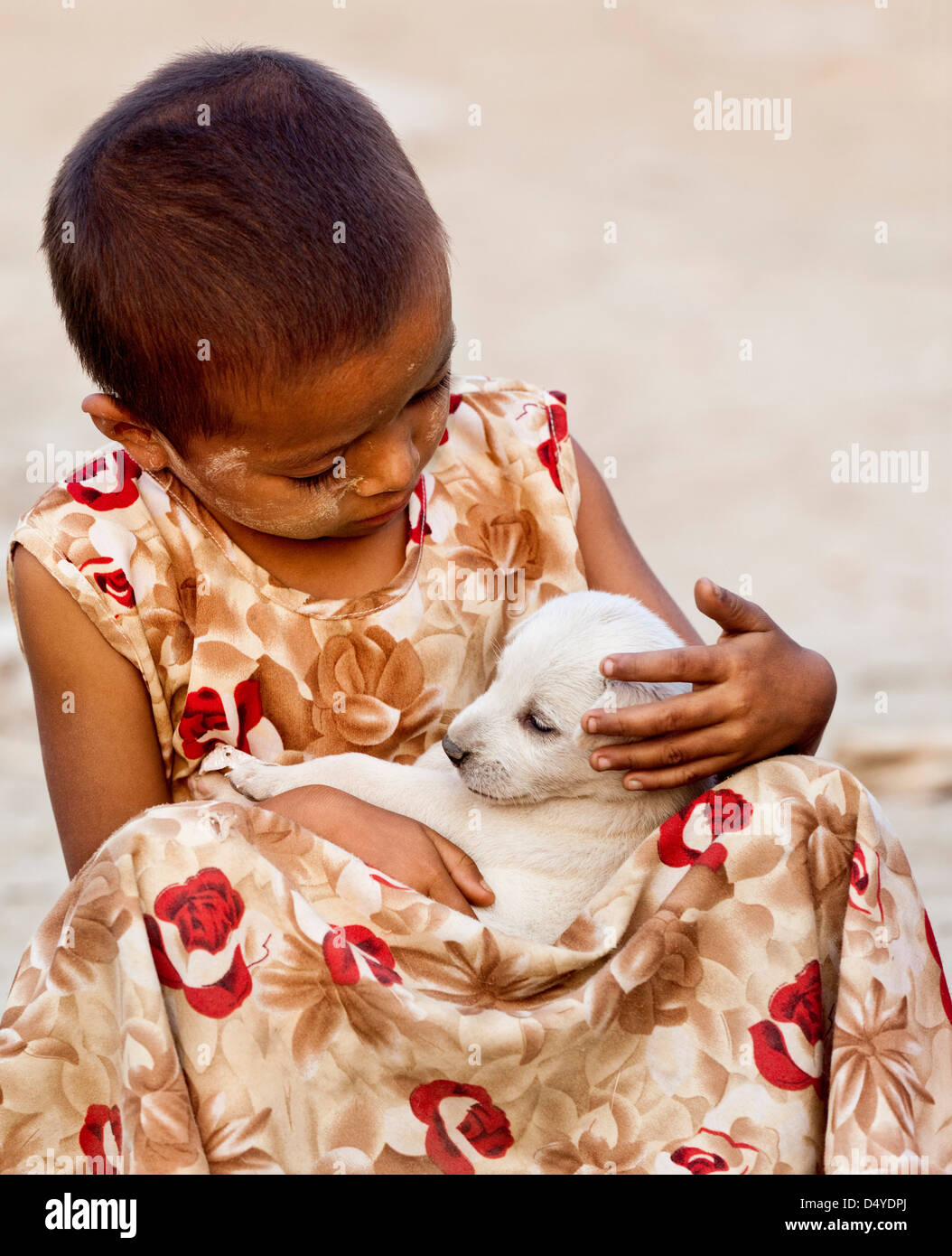 A girl tenderly cradles a puppy, Mandalay, Myanmar. - Stock Image