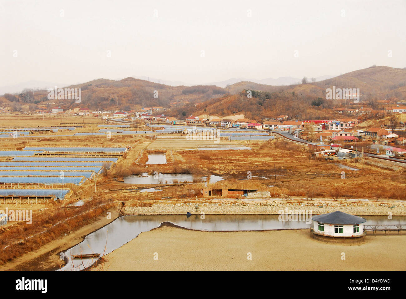 China, Dandong, elevated view of a salt pond with human settlement and mountains in the background - Stock Image
