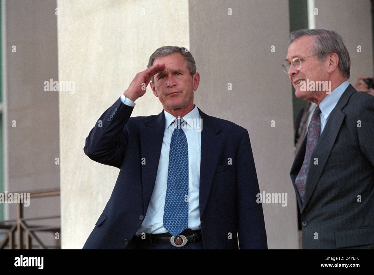 President George W. Bush salutes Wednesday, Sept. 12, 2001, as he leaves the Pentagon with Secretary of Defense - Stock Image