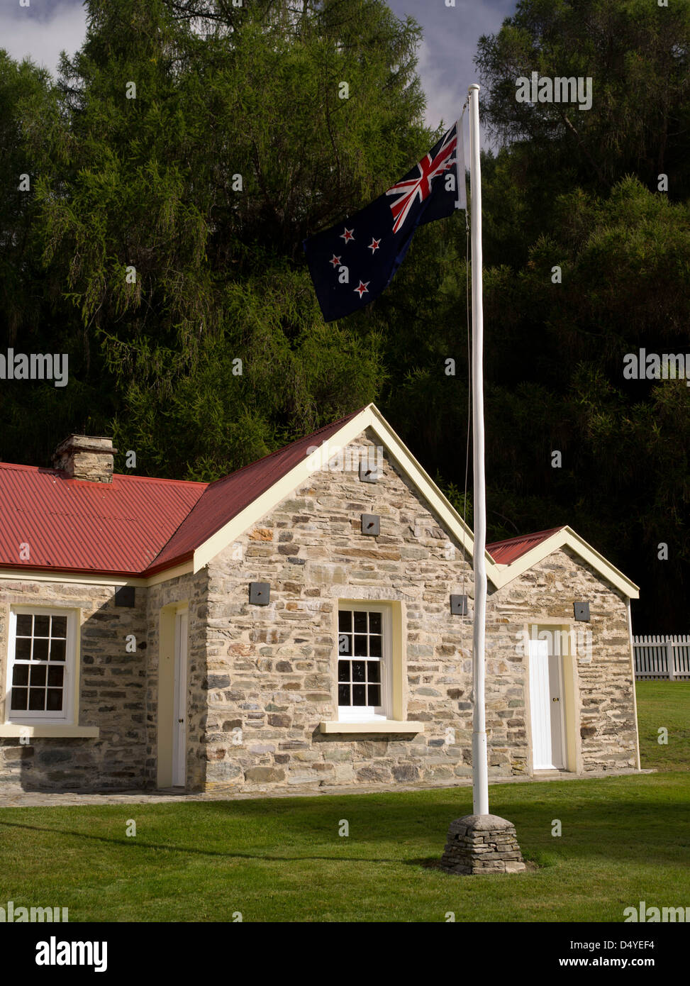 The historic Skipper's Point School and blowing NZ flag, near Queenstown, Otago, New Zealand. - Stock Image