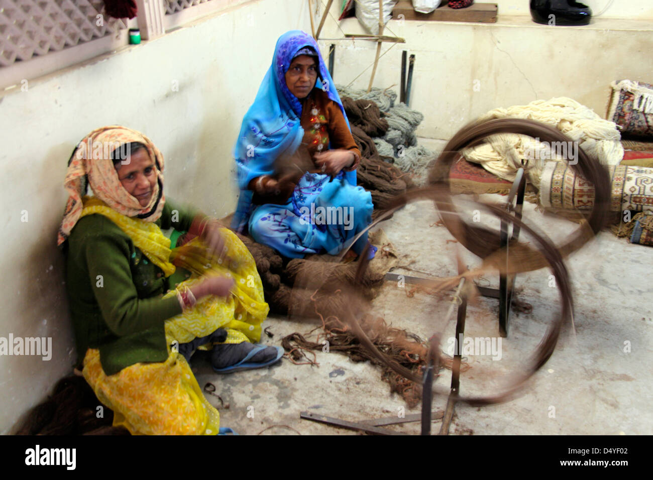 India, Jaipur. Indian women spinning wool for use in making carpets. - Stock Image