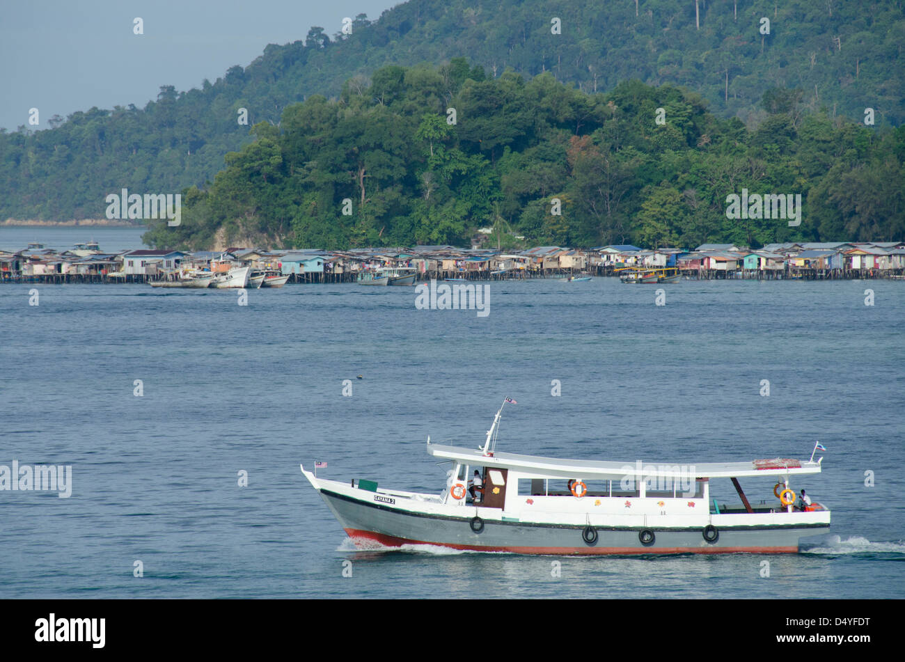 Malaysia, Borneo, Sabah, Sultan Sea, Kota Kinabalu. Boat in front of traditional 'water village'. - Stock Image