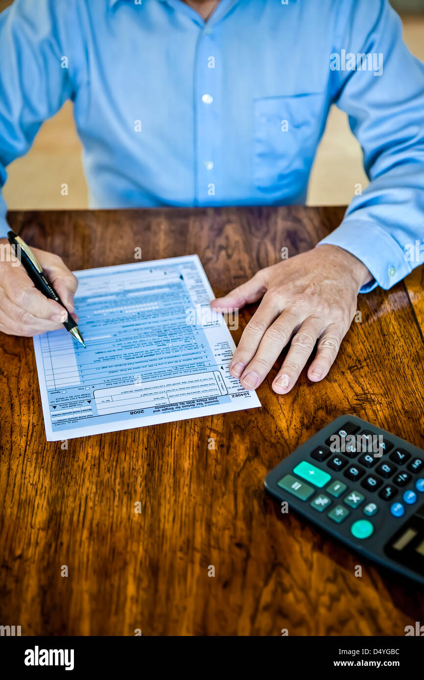 Older man with age spots on hands with US Federal tax form on wooden table with pen and calculator - Stock Image