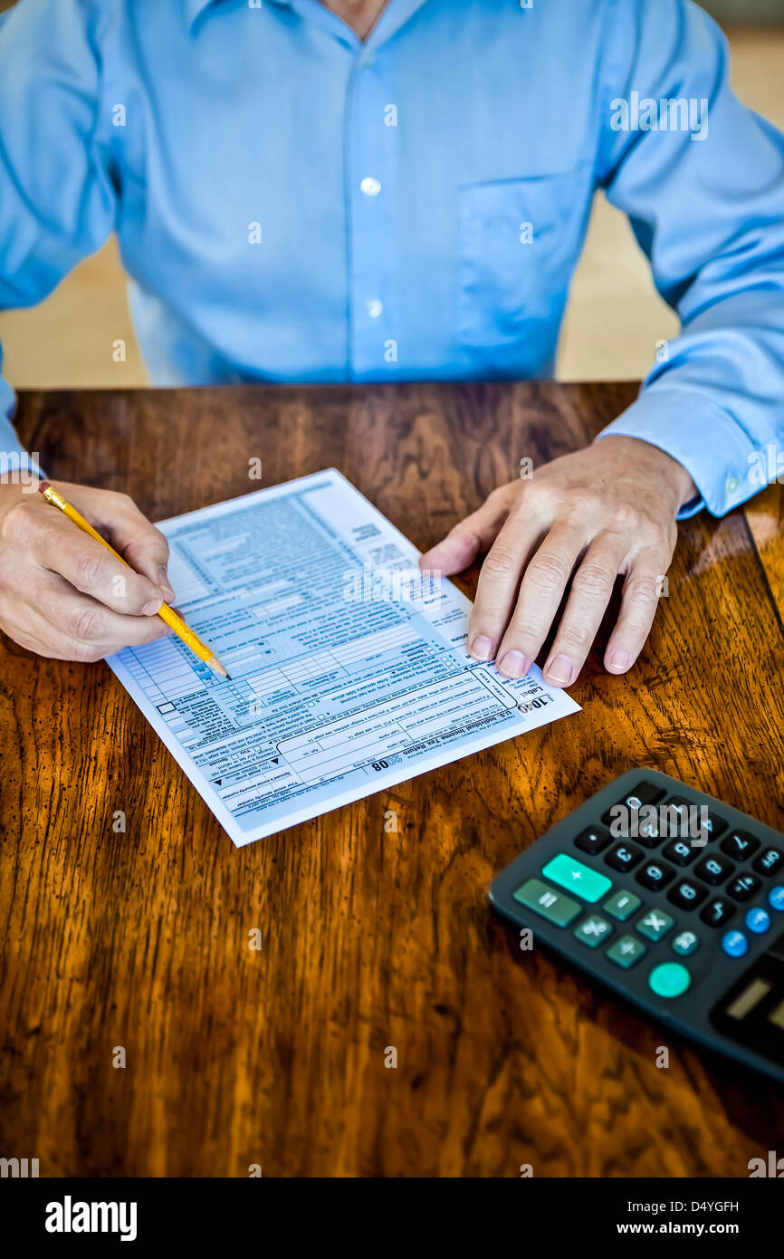 Older man with age spots on hands with US Federal tax form on wooden table with pencil and calculator - Stock Image