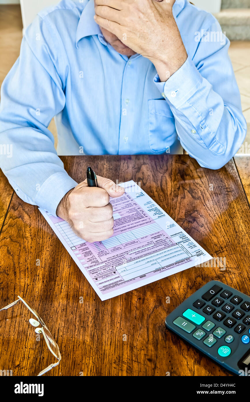 Older man with age spots on hands with US Federal tax form on wooden table with pen in clenched fist and calculator - Stock Image
