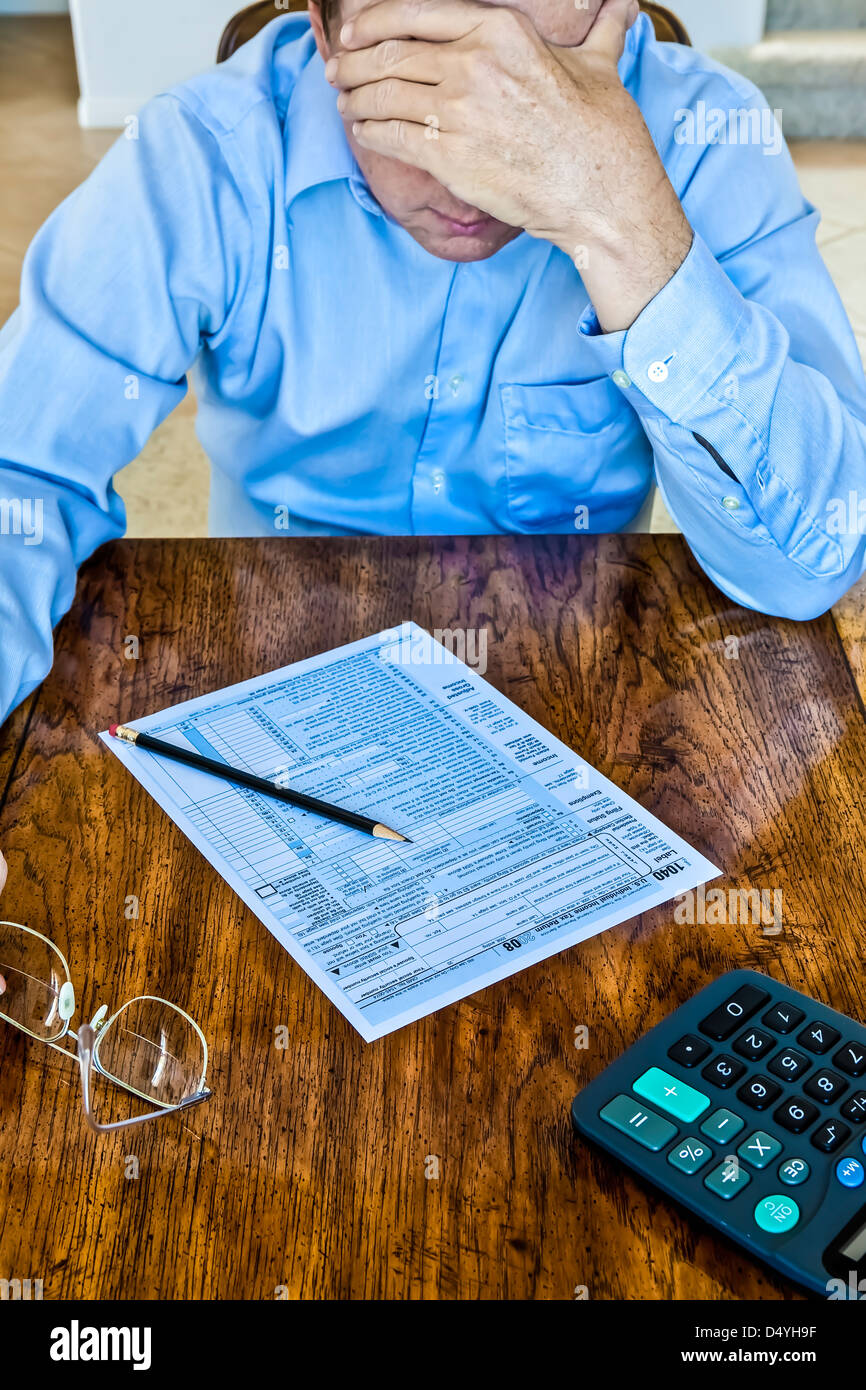 Older man with age spots on hands with US Federal tax form on wooden table with pencil and calculator and reading - Stock Image