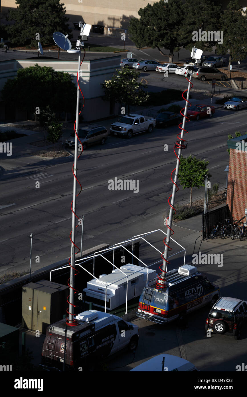 Two broadcast vans with masts extended. - Stock Image