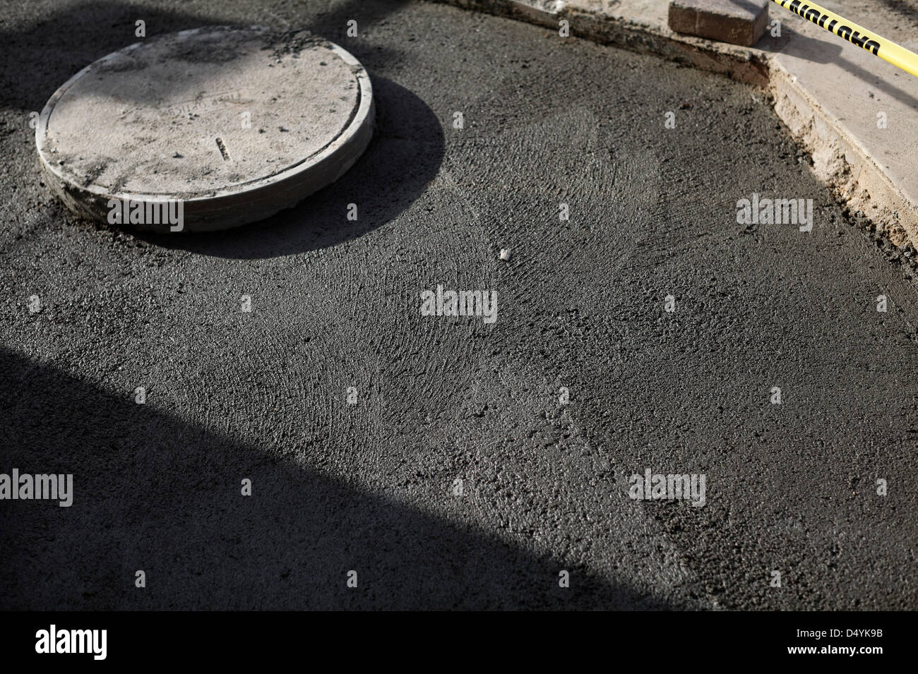 Freshly-poured concrete and utility access cover. - Stock Image