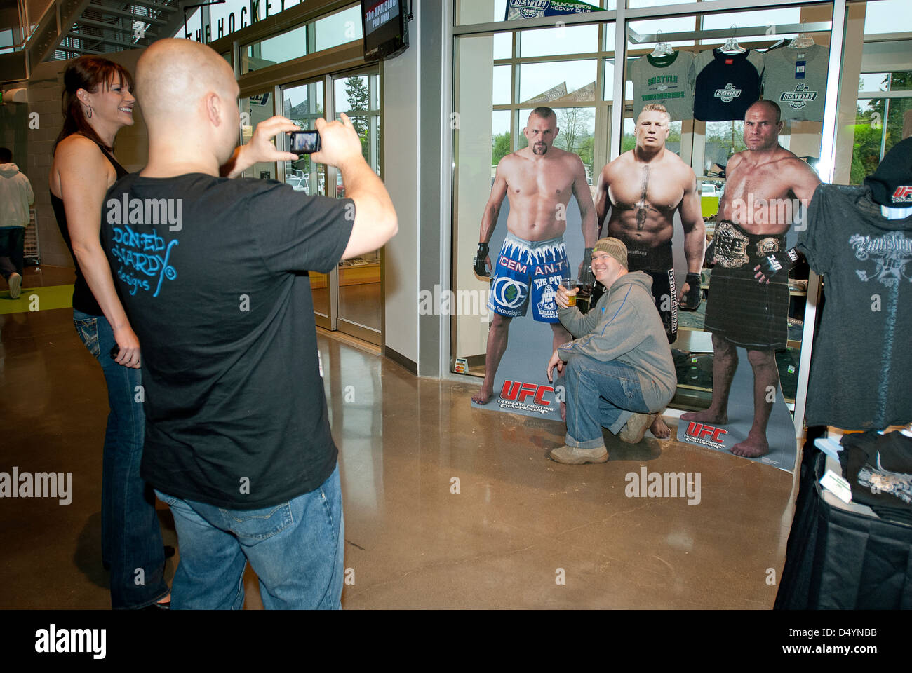 Fans posing in front of UFC life-sized cardboard stand. - Stock Image