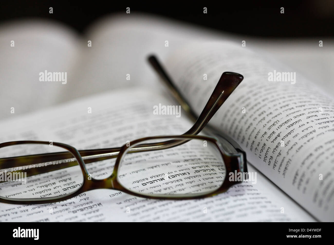 A Hebrew dictionary open at the word 'to love', viewed through spectacles - Stock Image