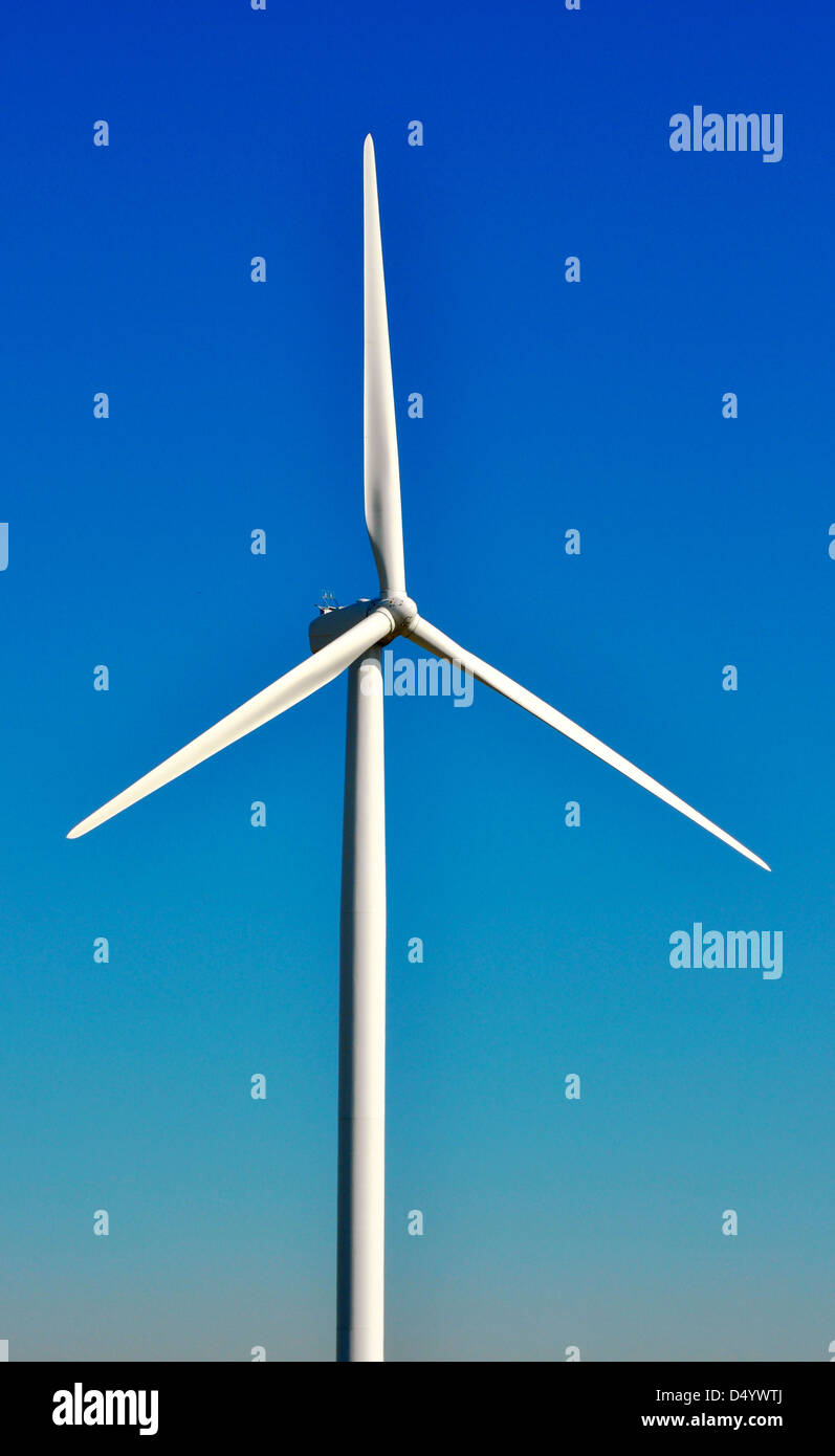 A windmill farm rotates over a Northwestern Indiana farm field. - Stock Image
