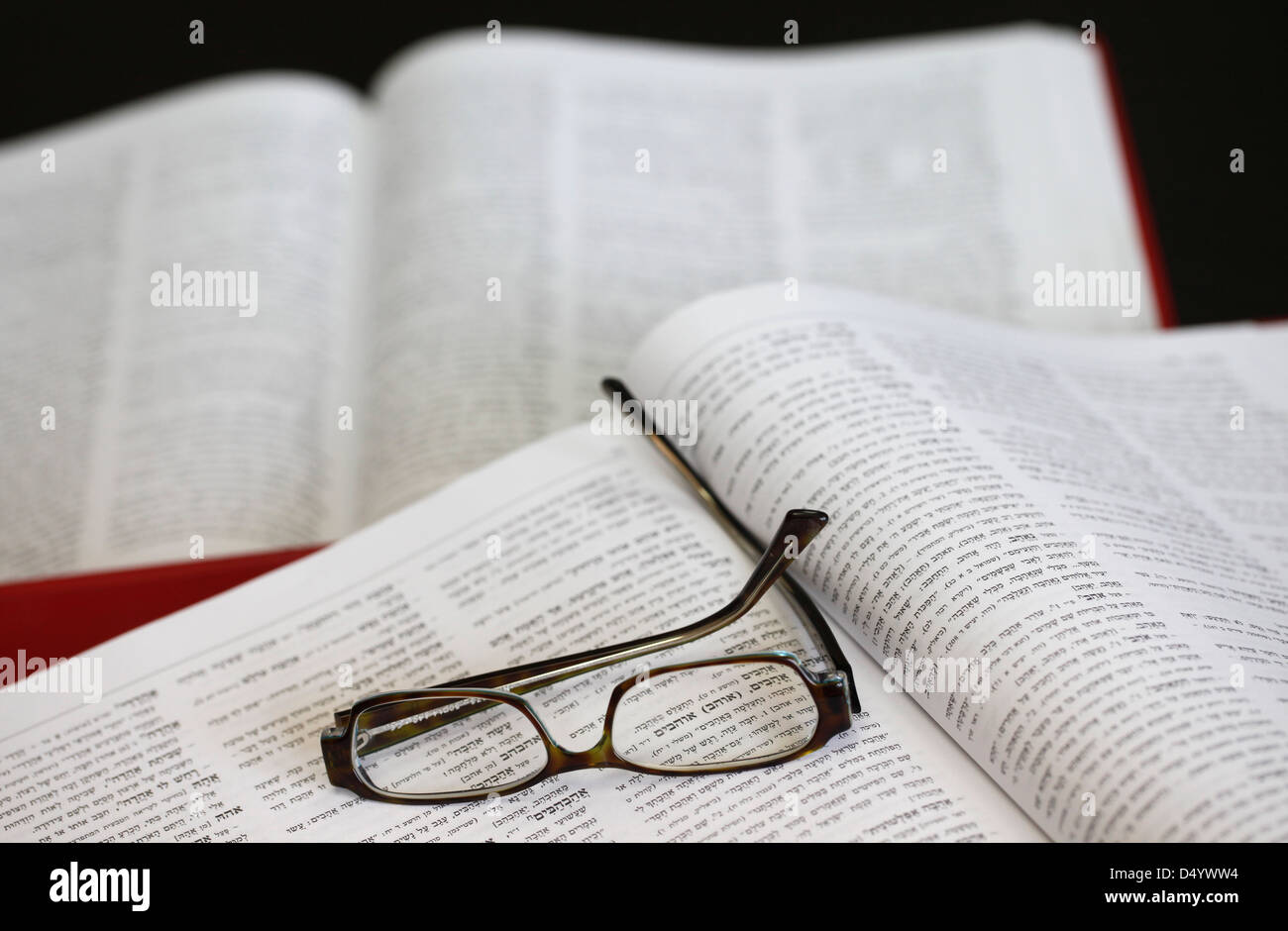 A Hebrew dictionary open at the word 'love', viewed through spectacles - Stock Image