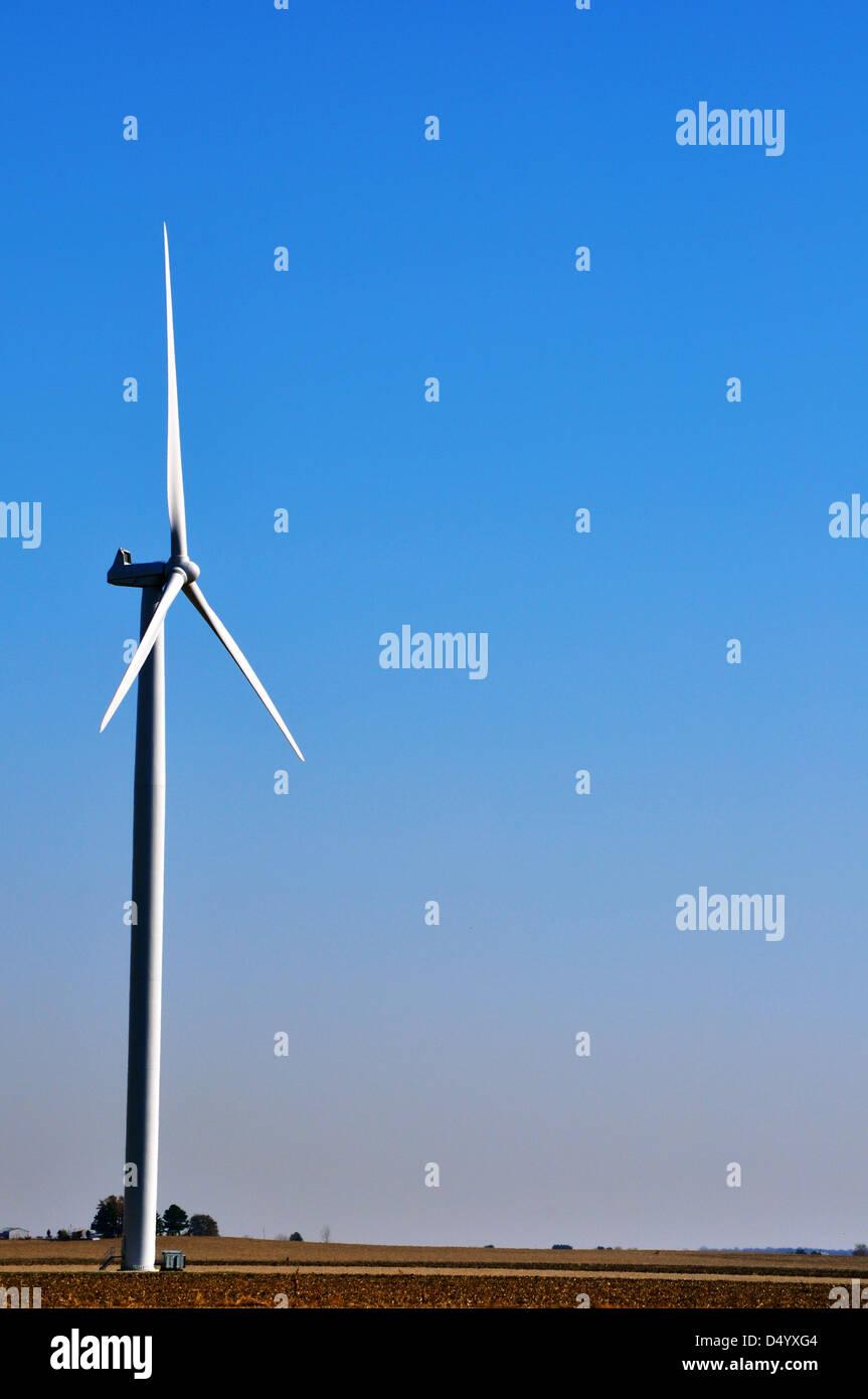 A windmill farm rotates over a Northwestern Indiana farm field. - Stock Image