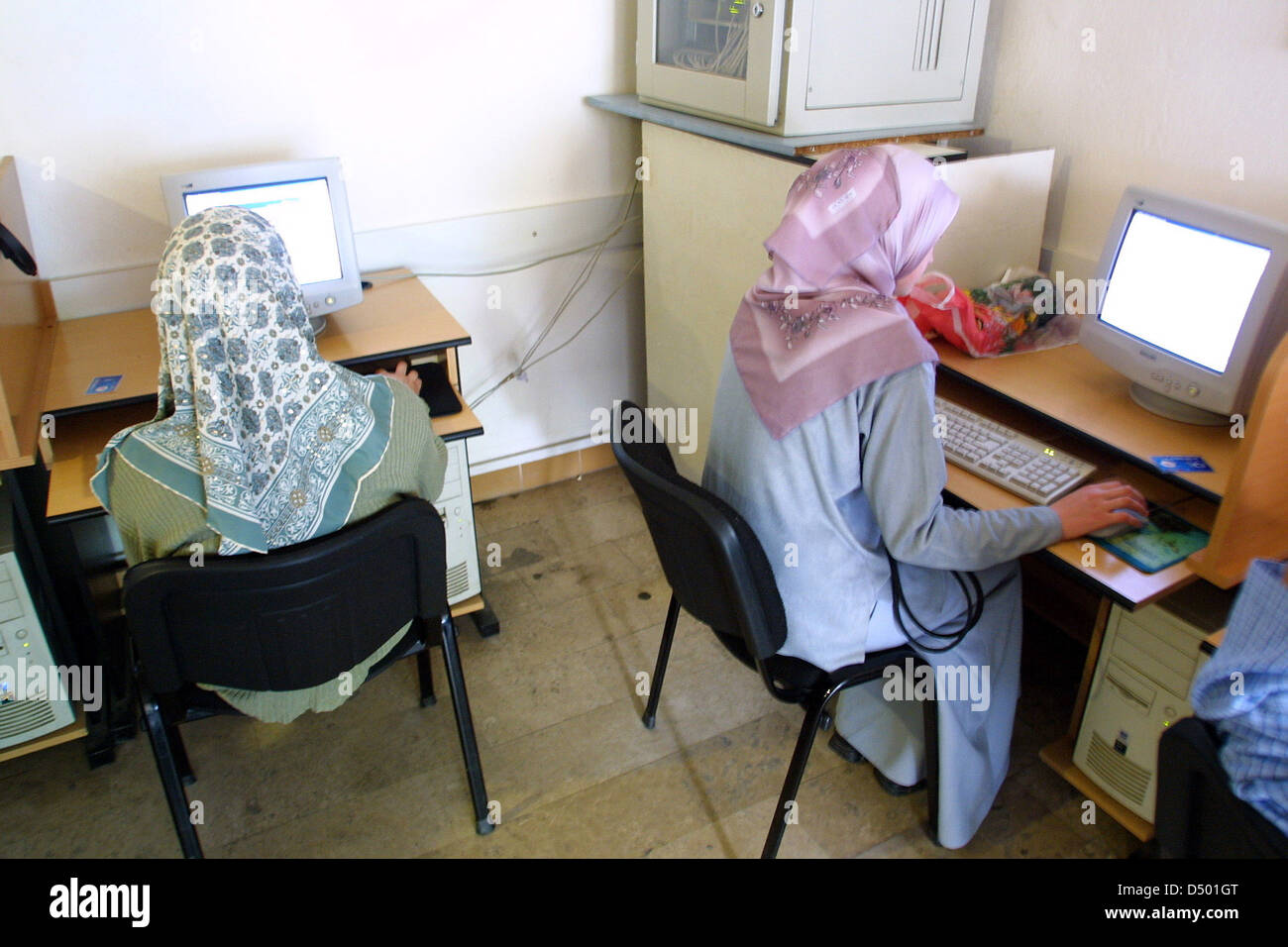 NOVI PAZAR, SERBIA, 29 APRIL 2002 ---- A traditionally dressed Moslem woman surfs the internet at an internet cafe Stock Photo