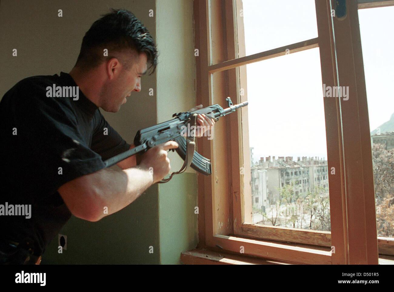 MOSTAR, BOSNIA, 17 AUGUST 1993 --- A Bosnian Croat soldier shoots out of a window at Bosnian Moslems defending their - Stock Image