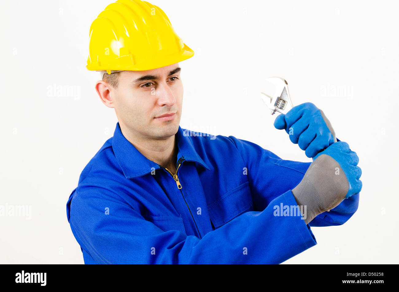 A man wearing protective equipment holding adjustable wrench Stock Photo