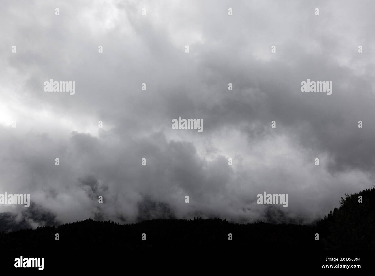 Grey clouds hover over the alpes. - Stock Image