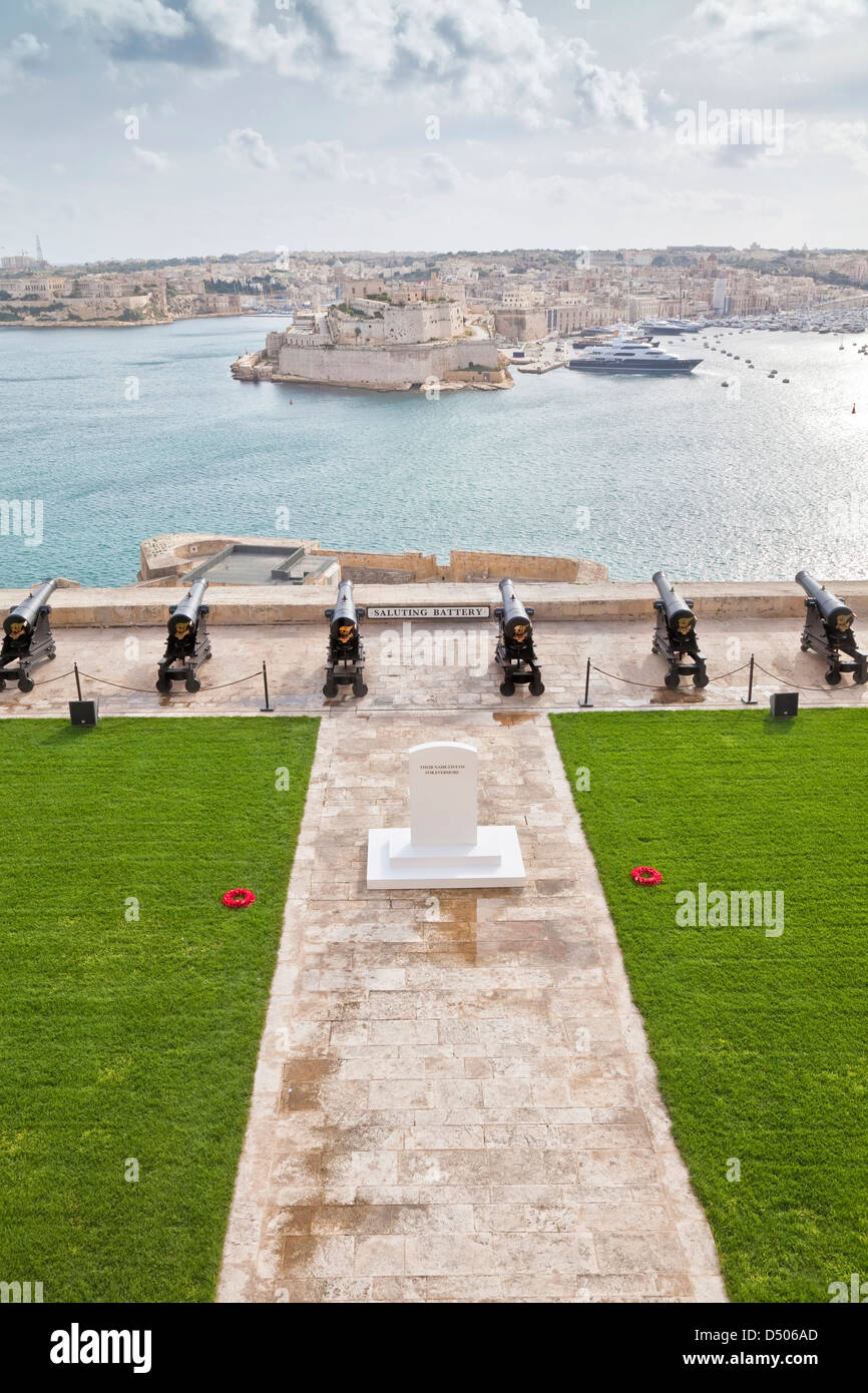 Cannons overlooking the Valletta Grand Harbor, Malta on Remembrance Day with the memorial in the foreground. - Stock Image