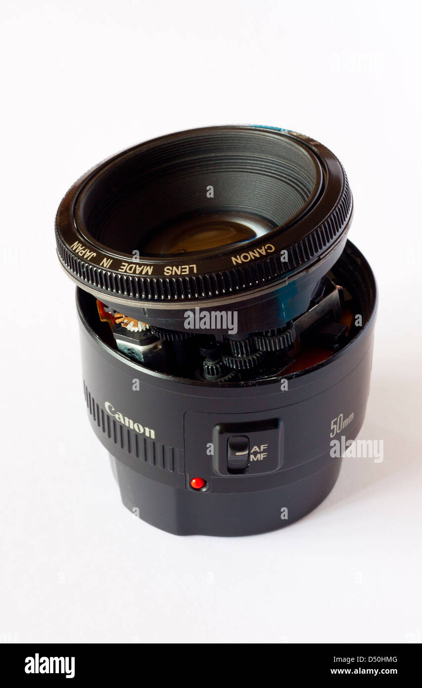 Close up view of damaged Canon Eos 50mm slr lens showing the internal workings and autofocus motor and cracked casing - Stock Image