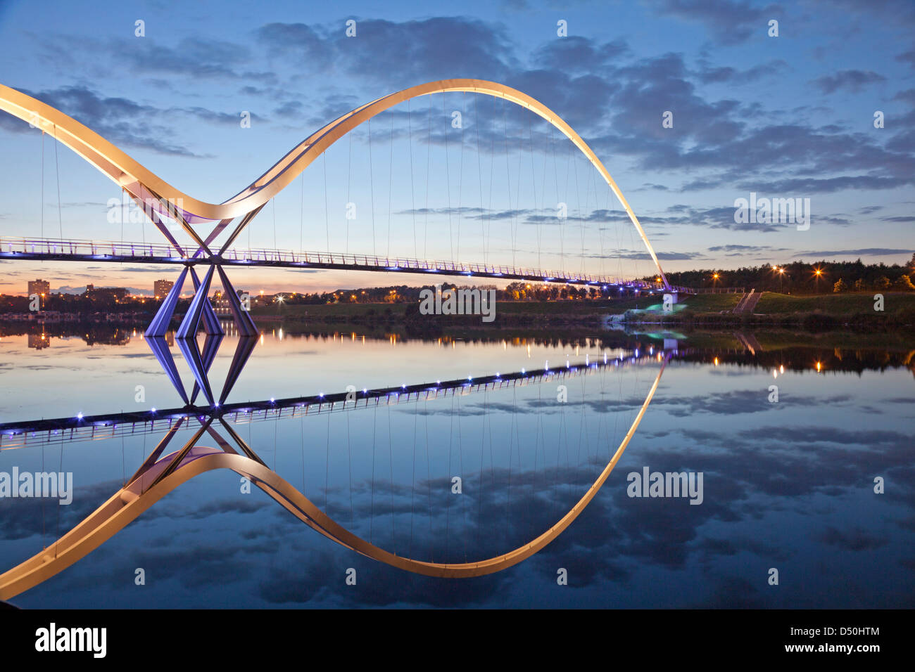 The Infinity bridge, Stockton-on-Tees, reflected in the river Tees at sunset. - Stock Image