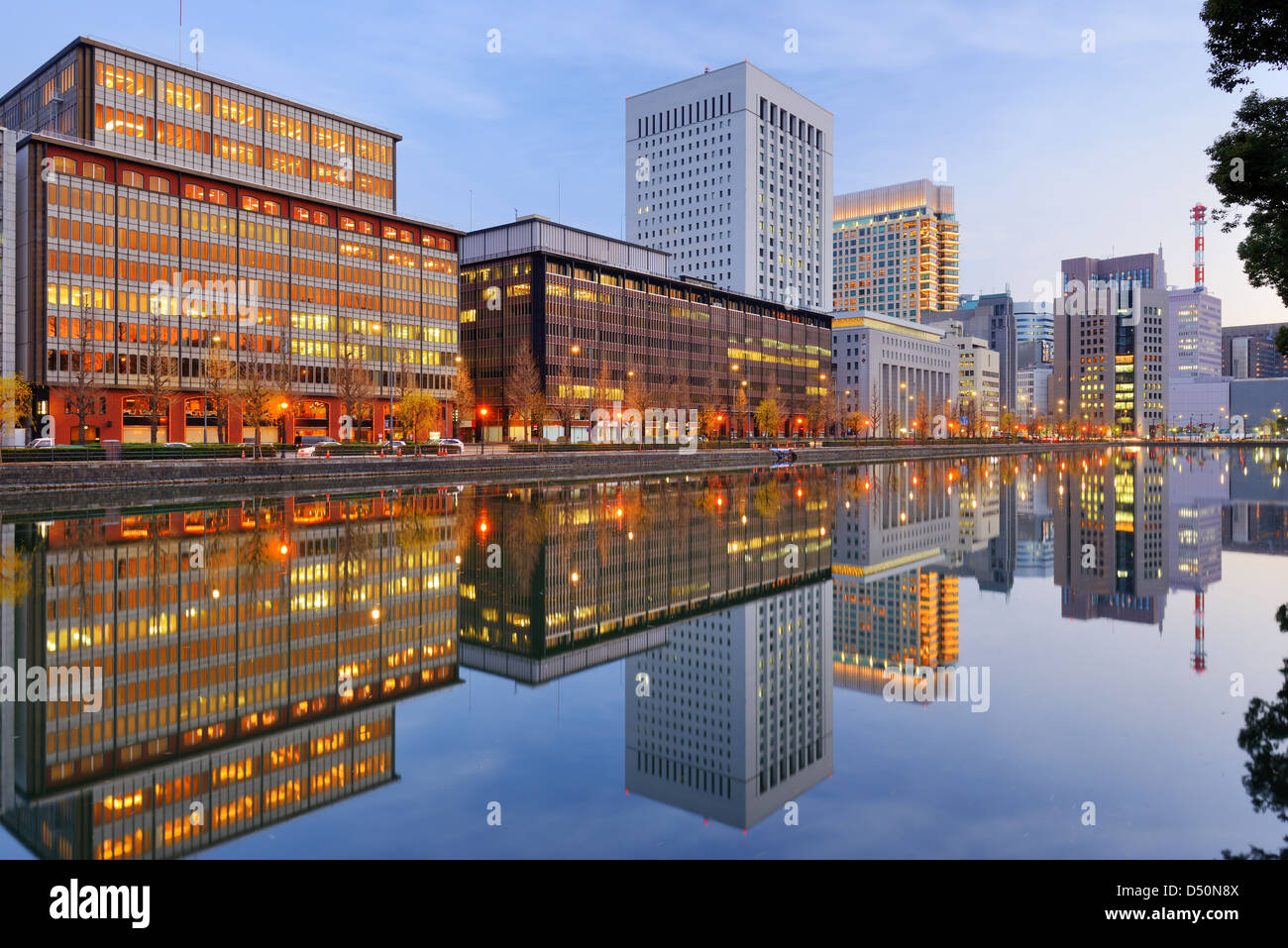 Landmark buildings reflect off the Imperial Palace moat in the Marunouchi district of Tokyo, Japan. - Stock Image